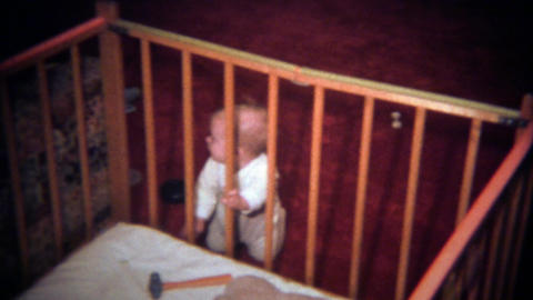 1979: Caucasian baby reaching for dangerous hammer in crib Footage