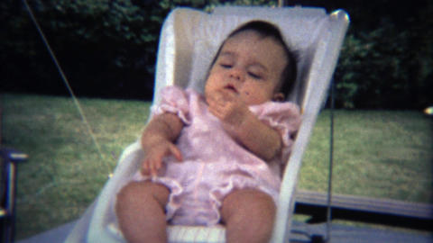 1971: Baby flailing legs and arms around in small white chair Footage