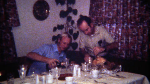 1971: Gay men couple carving turkey pouring wine for holiday celebration Footage