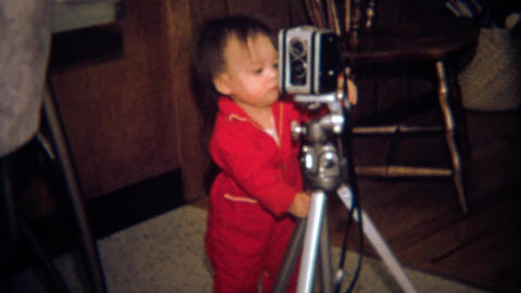 1971: Toddler Photographer Learning The Craft Looks At 8mm Movie Camera stock footage