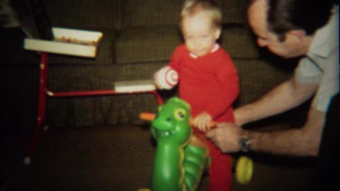 1974: Grandpa plays with baby on turtle toy scooter Footage