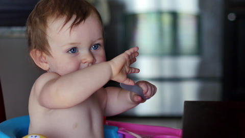 Cute baby dances and smiles while eating dinner, 4K Footage