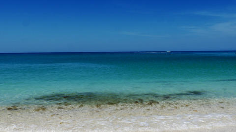 Jet ski crosses frame on beautiful blue beach, 4K Footage