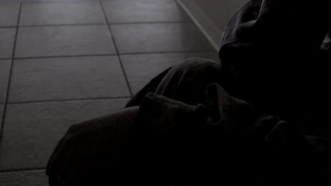 Closeup of soldier's hands while he sits in hallway, 4K Footage