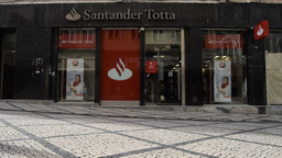 People walk past the Coimbra branch of Santander Totta bank in Portugal Footage