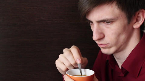 A young guy with an orange mug in his hand stirs a teaspoon looks aside ビデオ