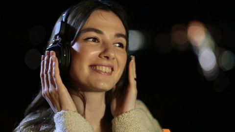 Girl listening to music with headphones at night Footage