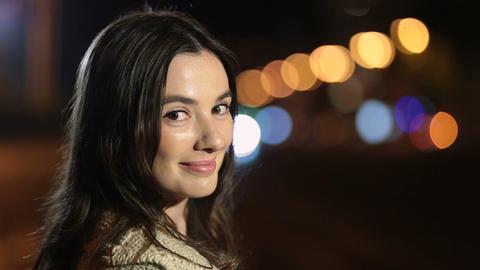 Playful smiling woman flirting on street at night Footage