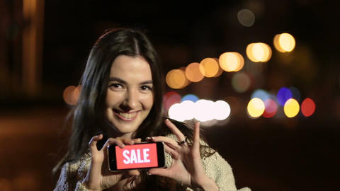 Girl holds phone with sale ad on screen at night