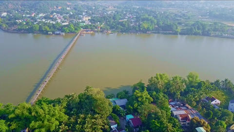 Aerial Motion from Town across River with Narrow Bridge Footage