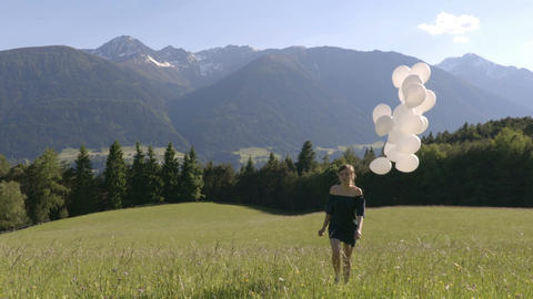 Girl walk with balloons in the field with the mountains on the background Footage