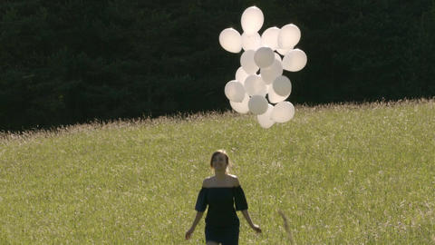 Girl jump with bunch of balloons in field summer time Footage