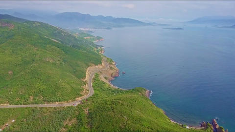 Aerial View Highway among Hills and Ocean against Mountains Footage