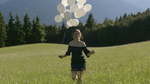 Girl running in the green field with balloons Footage