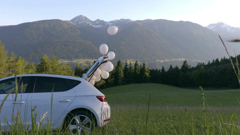 White balloons are flying out of the white car in the sky Footage
