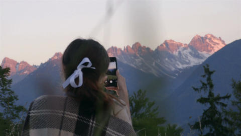 Girl is taking photos of the sunset in alps Footage