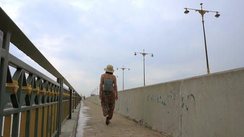 Women crossing the concrete bridge. (Panning shot) ビデオ