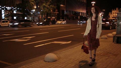 Positive fashionable woman walking on night street ビデオ