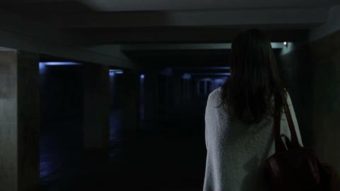 Frightened woman running through dark underpass Footage
