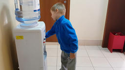 The child draws water from the cooler and drinks water