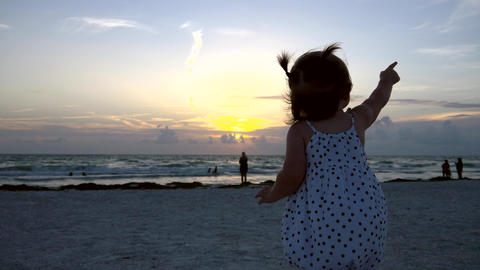 Cute little girl waves and points at helicopter at the beach, 4K Footage