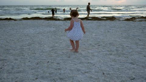 Little girl walks through sand towards sunset, 4K Footage