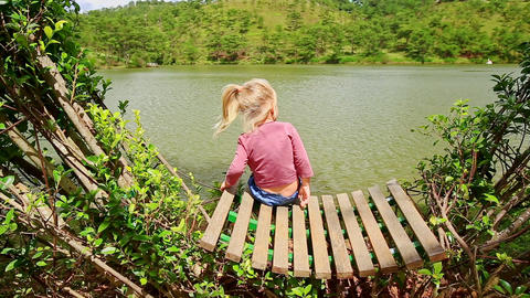 Closeup Little Girl Sits on Bench In Clipped Bush Watches Lake Footage