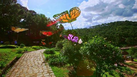 Stone Walkway among Big Butterflies Sculptures in Tropical Park Footage