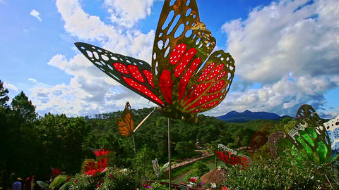 Stone Walkway among Big Butterflies Sculptures in Tropical Park Footage