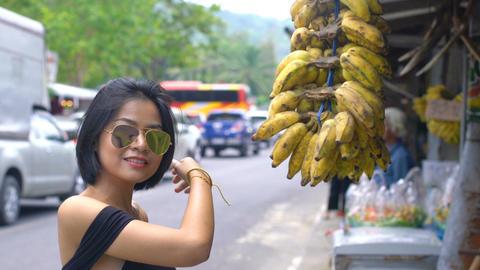 Young asian woman buying bananas at market Footage