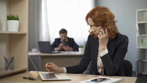 Businesswoman sitting at work desk and talking over mobile phone, negotiations Footage