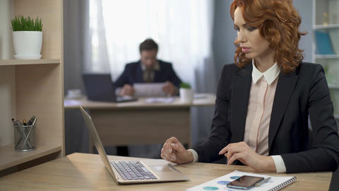 Female employee in suit sitting at work desk and typing on computer, office work Footage