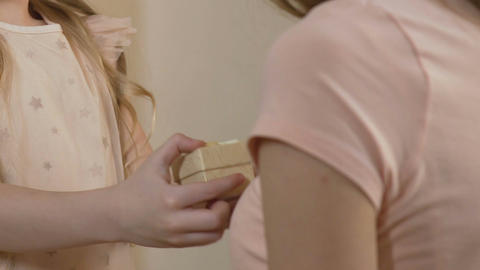 Close-up of little daughter giving a gift to mother, family values, relations Footage