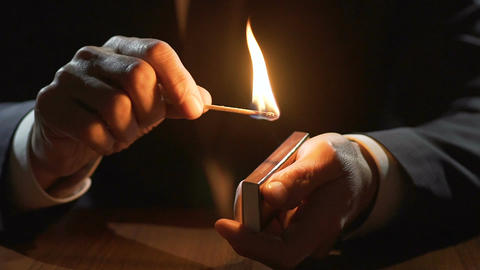 Male hands holding matchbox and burning match, life passes by fast, slow motion Footage