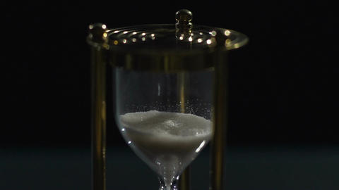 Sand dropping in hour glass, precious time flies, transience of life, slow-mo Footage