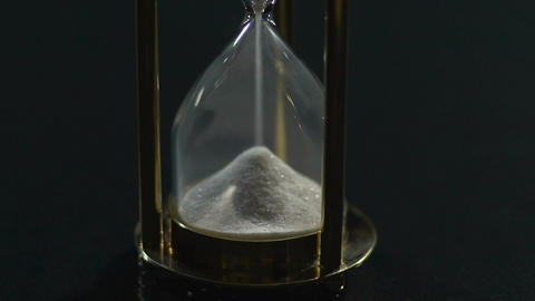 White sand flowing in hourglass, past and future, transience of life, close-up Footage
