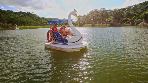 Moving Closely Swan Pedal Boat with Family against Sunlight Footage