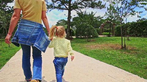 Blond Mother Little Girl Walk along Walkway in Tropical Park Footage