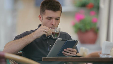 Man using Tablet and Drinking Coffee in Cafe Filmmaterial
