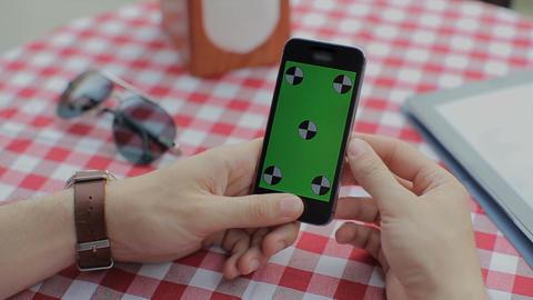 Man using smartphone in Coffee Shop. Smartphone with Green Screen ビデオ