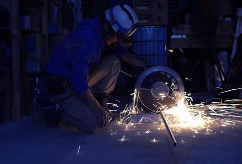 Electric wheel grinding on steel pipe in work space Foto