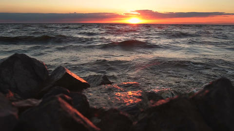 Red sky over a rocky seashore. Sunset landscape Footage