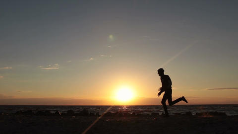 Silhouette of man running at seaside twilight time