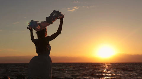 Silhouette of woman with scarf on beach at sunset Footage