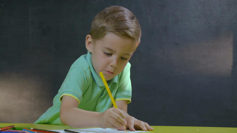 Little boy sitting at table and drawing with colored pencils Footage