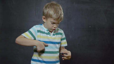 Boy showing skills by flicking spinners with finger 画像