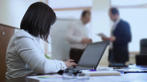 Female employee typing minutes on computer in meeting, men discussing project Footage