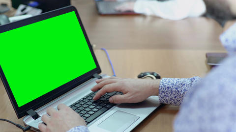 Male employee working on laptop with green screen at working desk in office Footage