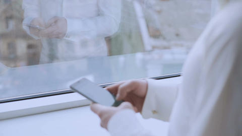 Male boss scrolling touchscreen on smartphone, readings news, window reflection Footage