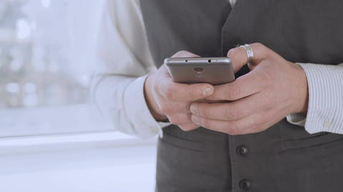 Smartly dressed man holding smartphone in hands, scrolling social media newsfeed Footage